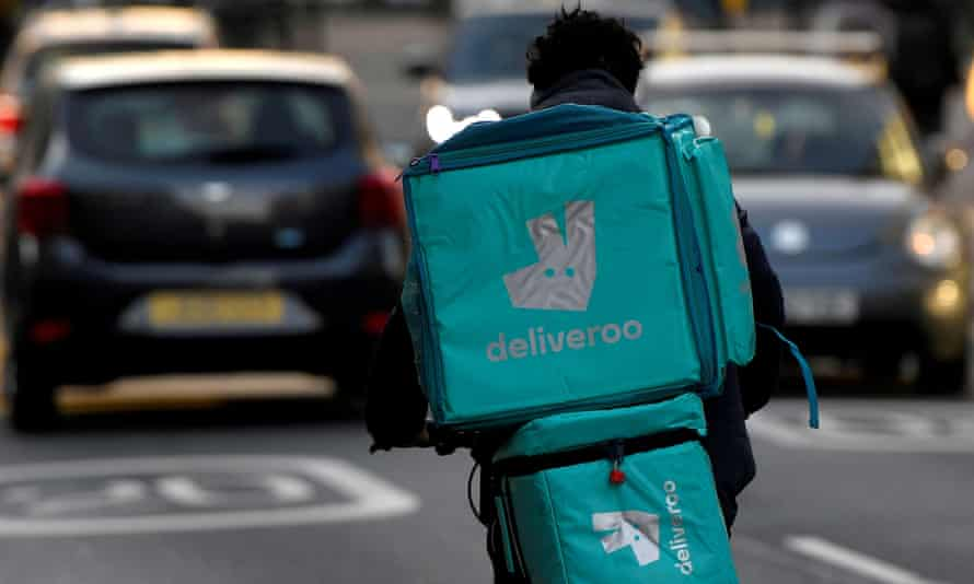 Deliveroo delivery rider cycles in London