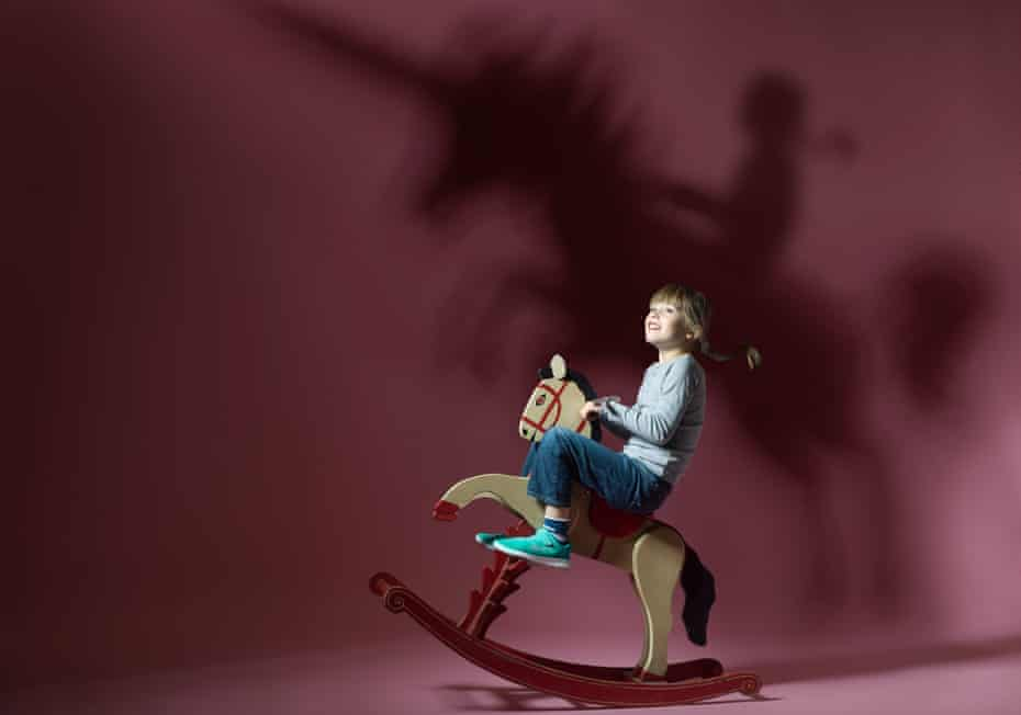 Robin, aged 6, on a rocking horse, the shadow of a unicorn behind her