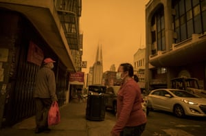 People wearing protective masks walk on Stockton Street in the Chinatown district of San Francisco.