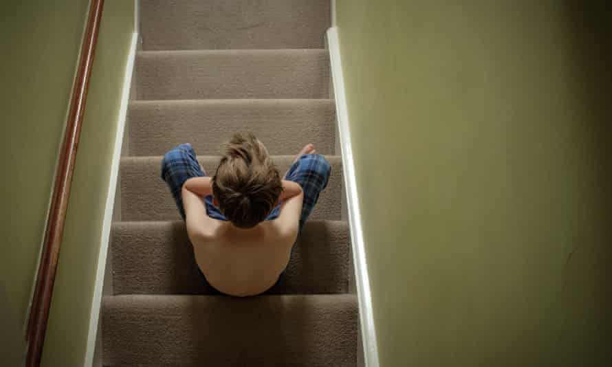 Child sitting on the stairs with head in his hands