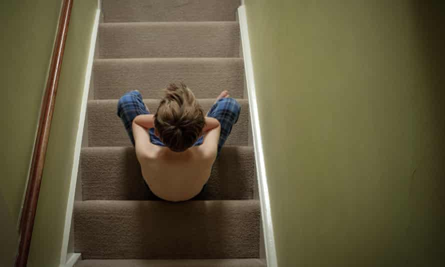 A child sitting on the stairs with his head in his hands looking upset.