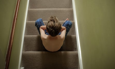 Boy sitting on stairs with head in hands