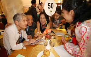 South Korea's Lee Geum-seom (L), 92, and her son Lee Sang-cheol (2nd from L), 71, look at family photos.