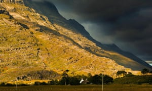 Liathach,  one of the Torridon hills, Wester Ross and a farm at the foot of a mountain in a plain heath seen at sunset in autumn