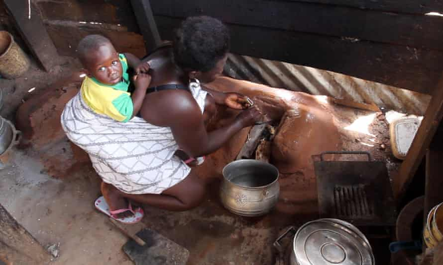 A woman in Ghana lights a fire for cooking while carrying a child on her back.