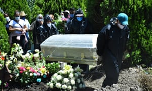 Cemetery workers wearing protective gear carry the plastic-wrapped coffin of a man who died from coronavirus at San Isidro cemetery, Mexico City.