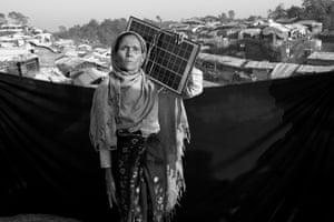 Hafaja, 60, holds a solar panel