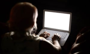 An anonymous woman sitting in the dark and using a laptop