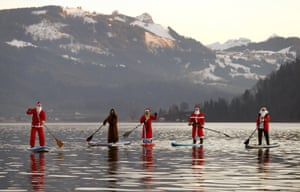 People dressed as Santa Claus pose on their stand-up paddles as they cross Lake Ägerisee