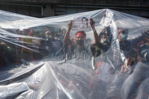 Protesters stand under plastic sheeting to protect themselves against police water cannon in Yangon