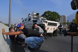 Civilians take cover during clashes with security forces in Caracas