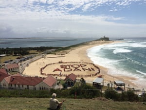People form a sign at Nobby's Beach in Newcastle as part of the Stop Adani protest