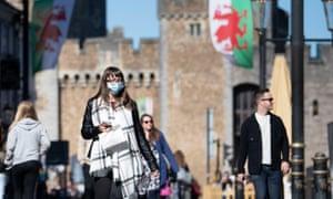 A woman wears a face mask near Cardiff Castle, Wales.