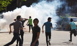 Egyptian protesters run for cover after police fire teargas during a demonstration in Cairo