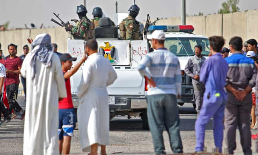 Iraqi security forces arrive to disperse a demonstration outside oilfields near Basra on 17 July.