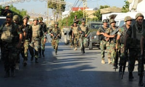 Lebanese army soldiers patrol near the site of suicide attacks in the Christian village of al-Qaa.