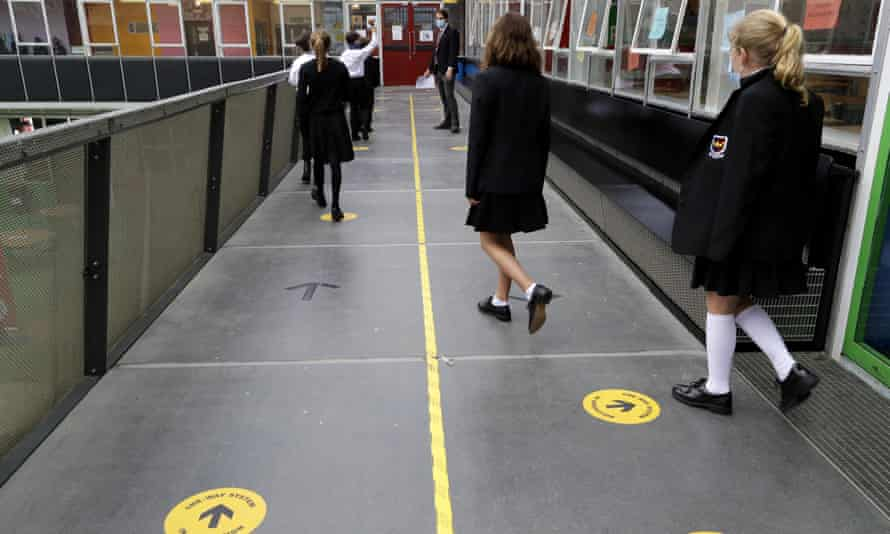 Pupils follow social distancing signs as they walk along a corridor at Kingsdale Foundation School in London