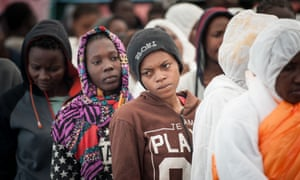 Migrants queue up after arriving by boat in Salerno, Italy.