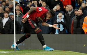 Manchester United's Fred is hit by missiles as he tries to take a corner during the derby.