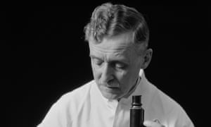 1920s 1930s MALE SCIENTIST WEARING WHITE LAB COAT WRITING DATA ON CLIP BOARD HOLDING FOCUS CONTROL OF MICROSCOPE<br>CMRPW0 1920s 1930s MALE SCIENTIST WEARING WHITE LAB COAT WRITING DATA ON CLIP BOARD HOLDING FOCUS CONTROL OF MICROSCOPE