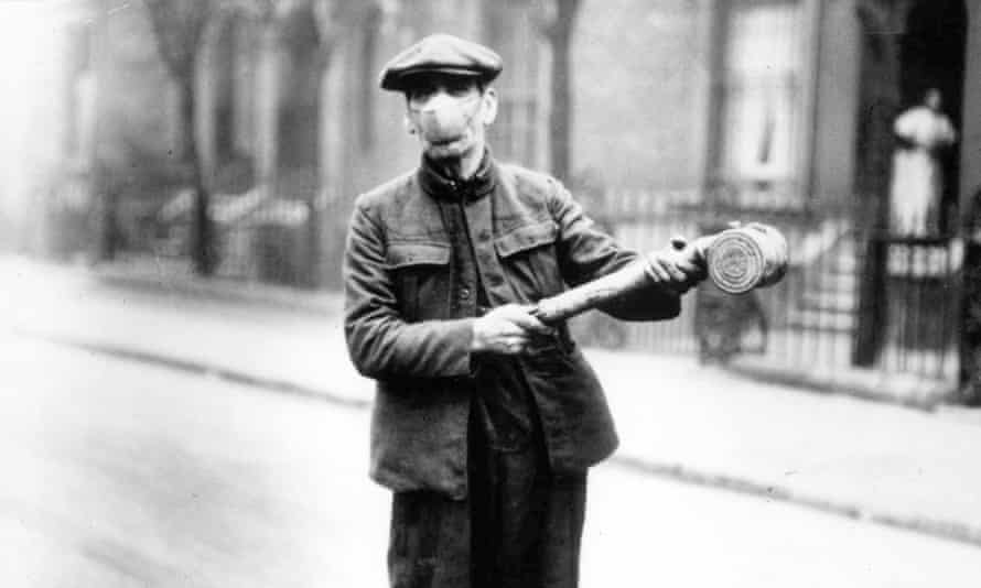 A man in a protective face mask with an anti flu spray, March 1920.