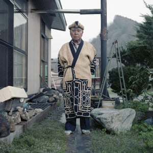 Kazunobu Kawanano is a proud Ainu Ekashi (elder) and an active member of the local Ainu community. He is pictured in front of his home, wearing a traditional Attush robe his wife Motoko weaved for him.