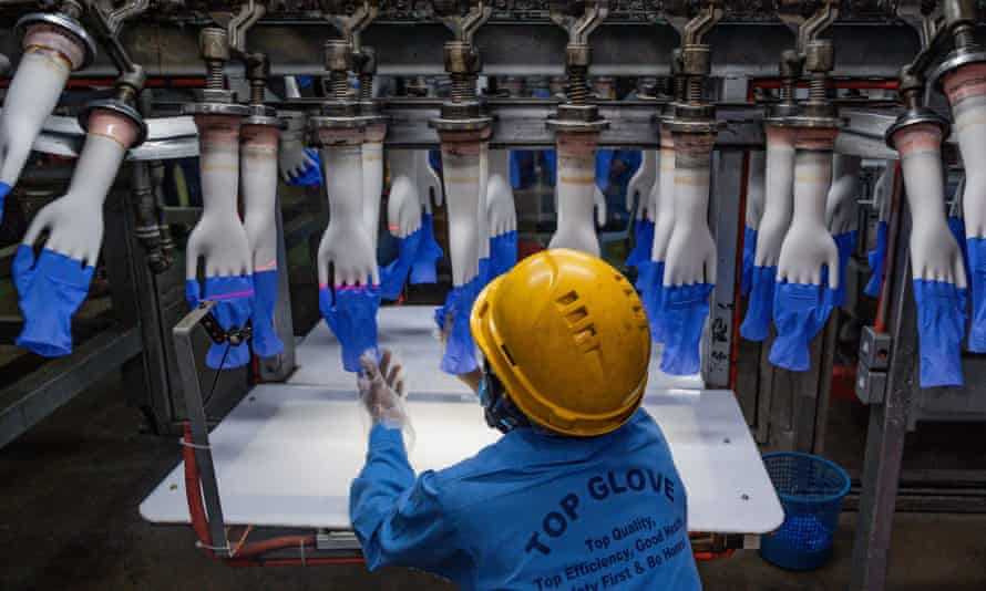 A worker inspects disposable gloves at the Top Glove factory production line.