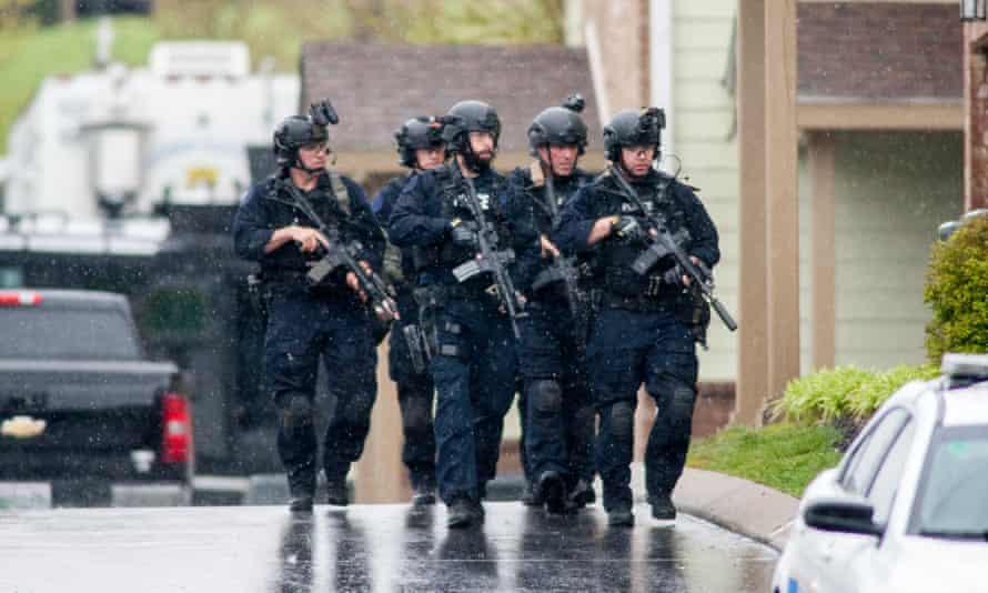 A Swat team and bomb squad serve a search warrant at the apartment of the suspected gunman.