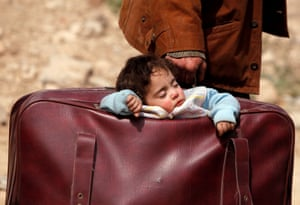 A child sleeps in a bag in the village of Beit Sawa in eastern Ghouta