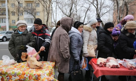 A queue to buy fresh raw meat from private vendors at a monthly street market in Kemerovo, Russia. State statistics have revealed the number of people living below the poverty line is increasing.