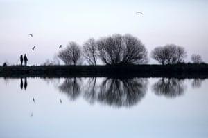 Holyrood, UK: A couple look out across Dunsapie Loch in Holyrood Park in Edinburgh