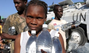 Haitians receive water at an aid distribution point after the earthquake in January 2010.