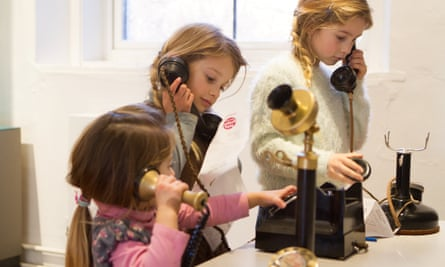 Three children try out telegraph exhibits at the Telegraph Museum in Cornwall, UK.