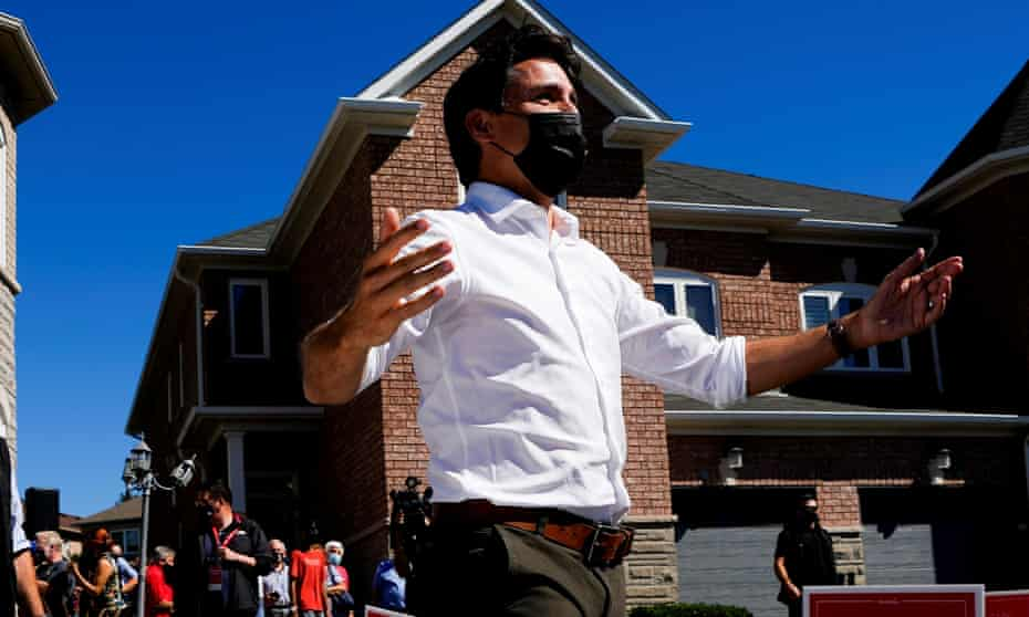 A masked Justin Trudeau greets potential voters under a blue sky in Vaughan, Ontario.