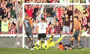 George Baldock of Sheffield United puts the ball past Swansea City goalkeeper Kristoffer Nordfeldt to score the opening goal of the game.