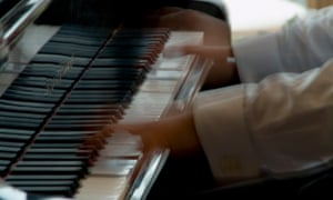 A player's hands speed over a piano keyboard