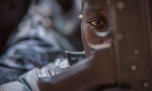 A newly released child soldier looks through a rifle trigger guard during a release ceremony for child soldiers in Yambio, South Sudan, in February 2018. More than 300 child soldiers, including 87 girls, have been released in the region of Yambio under a programme to help reintegrate them into society