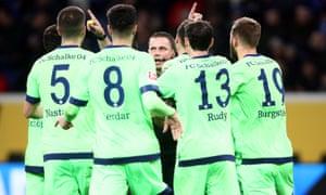 Referee Robert Kampka is surrounded by Schalke players of Schalke after awarding Hoffenheim a penalty.