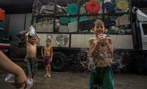 Children play with household plastic waste outside a sorting facility in Canumay West village in Valenzuela City, Manila, Philippines. 1 July 2019.