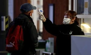 A man gets his temperature taken at Skoda Auto's factory as employees return to work following a shutdown due to the coronavirus outbreak.