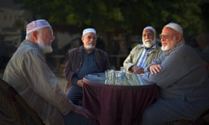 Photograph of four men in conversation sat around a table in a cafe in Monastir, Tunisia.