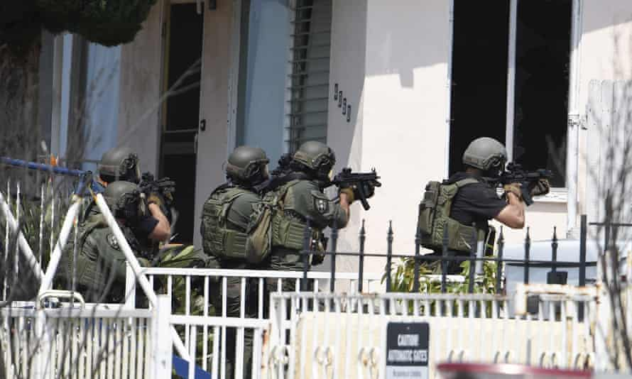 A Swat team prepares to enter the suspect's house.