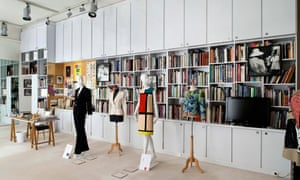 A display at the Musée Yves Saint Laurent in Paris. Mannequins wear a black trouser suit, a 1960s geometric-pattern colourful dress and also a white jacket, and stand in front of a wall of books and magazines.