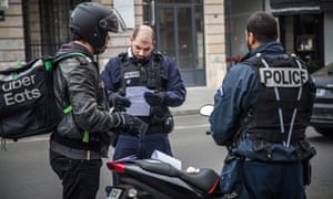 Officers check a motorcyclist's travel certificate.