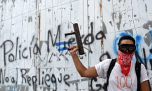 A masked young man holds a homemade mortar during  protests against the government of Nicaragua's president, Daniel Ortega.