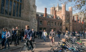 Cyclists and pedestrians move along Trinity Street past St Johns College, part of the University of Cambridge