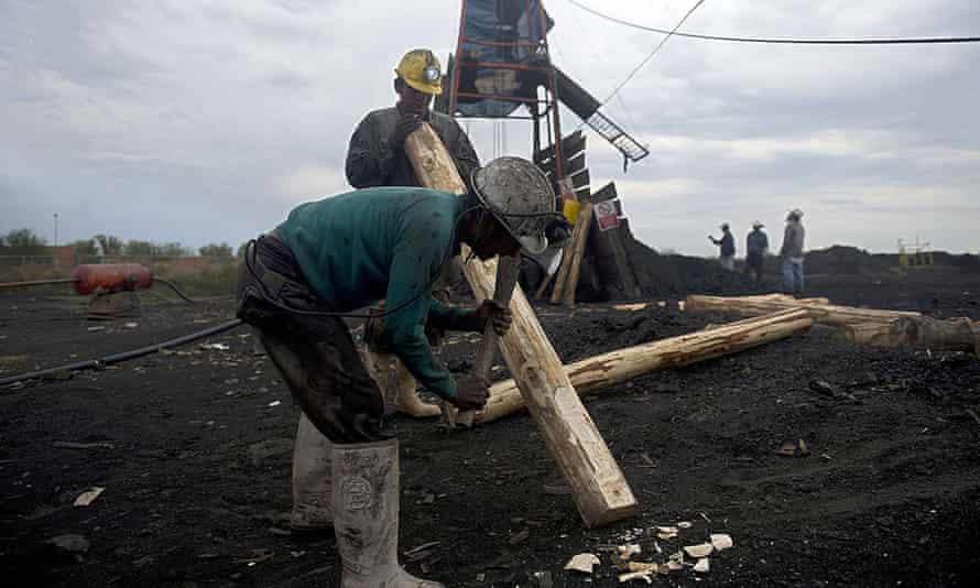 Miners make wooden support beams in a coal mine in Agujita, Coahuila state, on 13 November 2012.