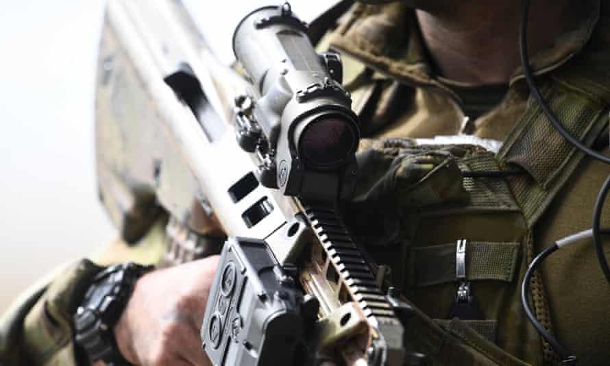 closeup of machine gun held by soldier