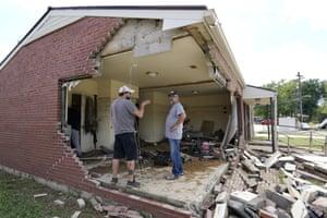 Men survey a damaged home in Waverly.