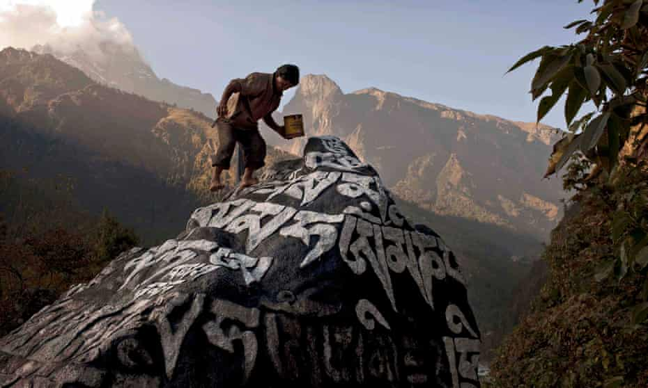A Nepali Sherpa touches up the paint on a large Mani stone, which contains Buddhist prayers, near the village of Phakding, in Nepal.